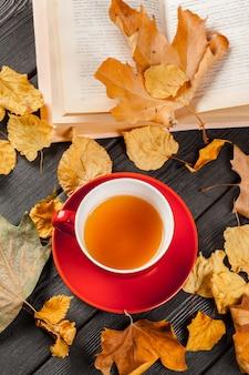 Tasse tee und herbstlaub auf dem tisch