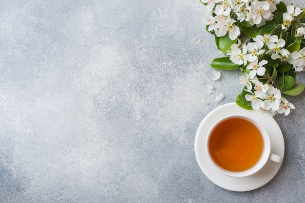 Tasse tee und hörnchen auf grau