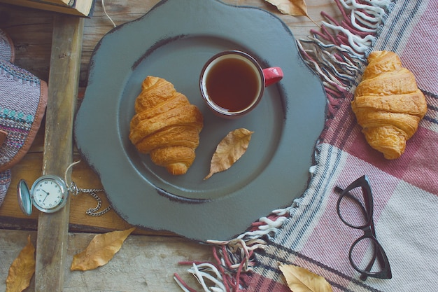 Tasse tee und hörnchen der französischen frühstückszusammensetzung der herbststimmung