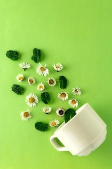 Tasse tee und kamille. natürlicher kräuterteekonzept. weiße tasse tee mit kamillenblumen.