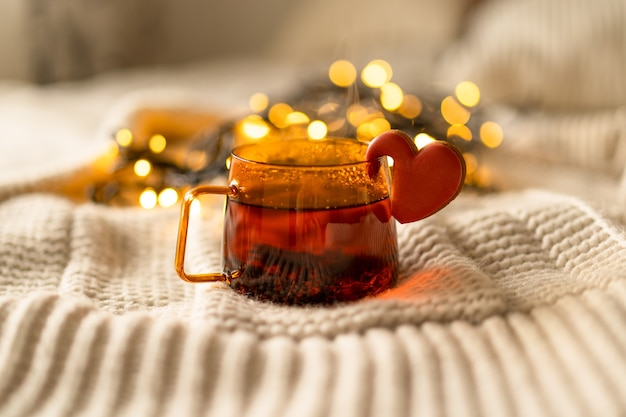 Tasse tee und kekse auf einem strickpullover