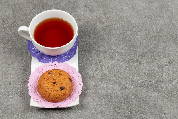 Tasse tee und kekse auf weißer untertasse
