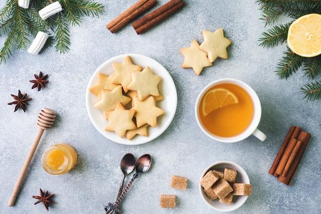 Tasse tee und kekse, tannenzweige, zimtstangen, anissterne