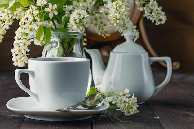 Tasse tee und kirsche auf hölzernem hintergrund