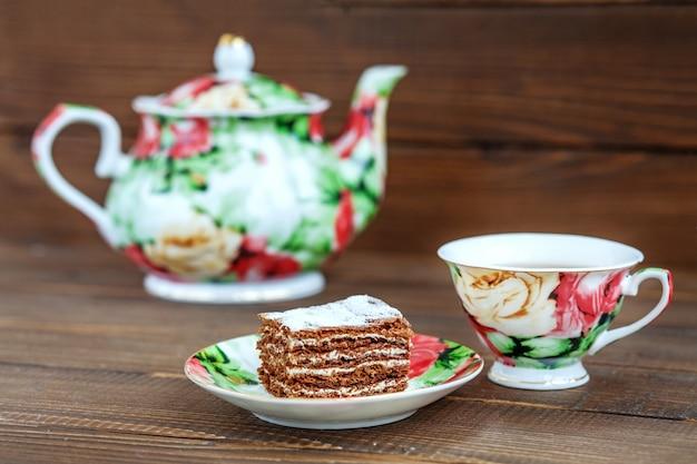Tasse tee und kuchen auf einem hölzernen hintergrund.