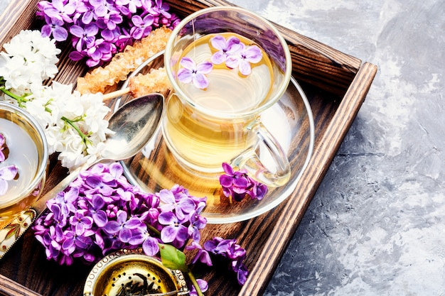 Tasse tee und lila blumen