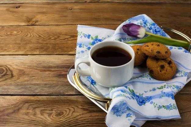Tasse tee und plätzchen auf teetablett