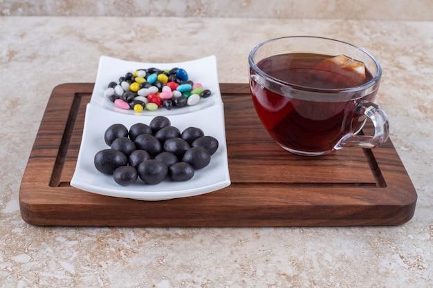 Tasse tee und pralinen auf holzbrett