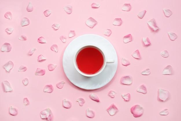 Tasse tee und rosa rosenblättern