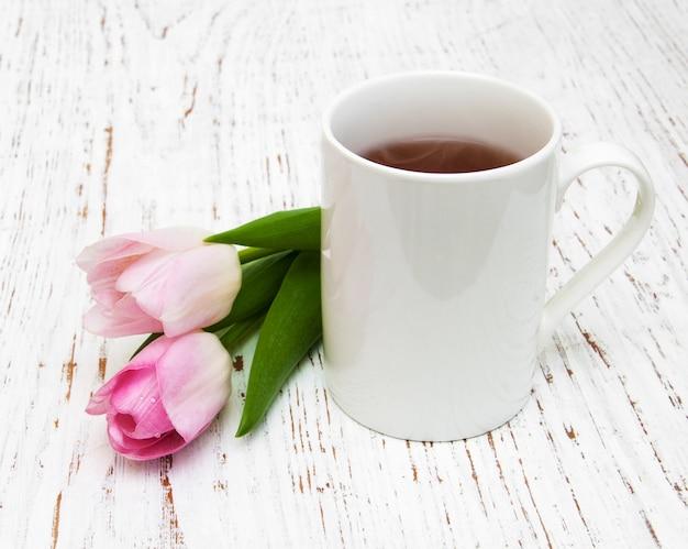 Tasse tee und rosa tulpen