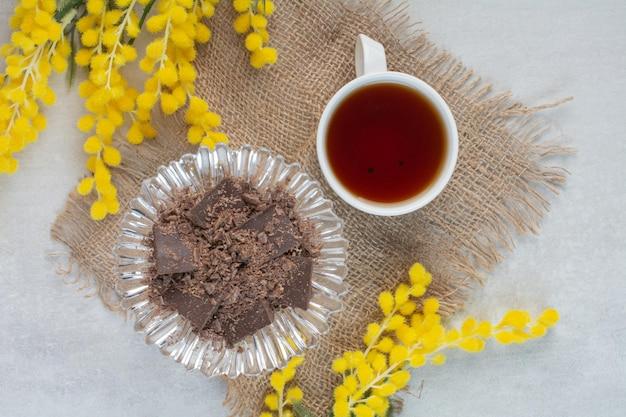 Tasse tee und schokoladenschüssel auf sackleinen mit blumen. foto in hoher qualität