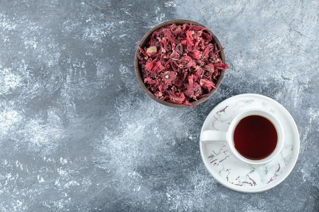 Tasse tee und schüssel mit getrockneten blütenblättern auf marmortisch.