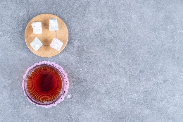 Tasse tee und süße bonbons auf marmoroberfläche