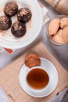Tasse tee und süße snacks auf dem tisch