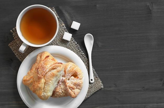 Tasse tee und süßer blätterteig mit marmelade auf einem dunklen holztisch