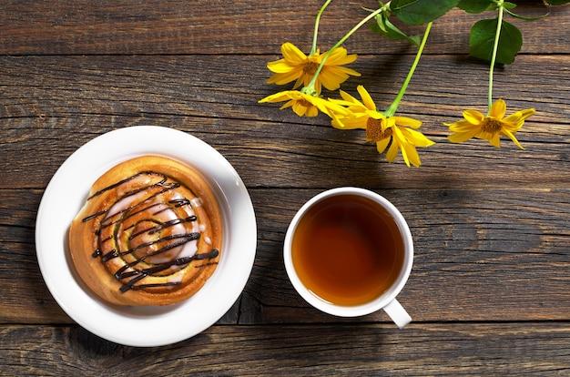Tasse tee und süßes brötchen auf holztisch mit blumen