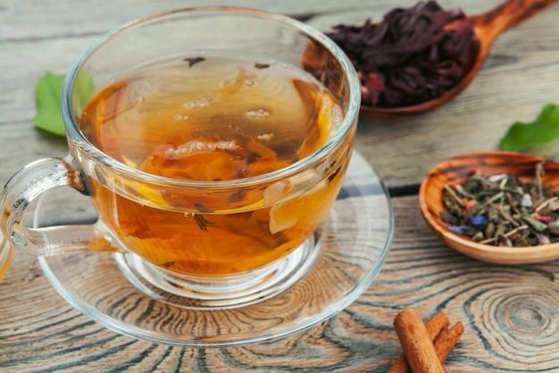 Tasse tee und teeblätter auf holztisch