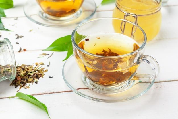Tasse tee und teeblätter auf weißem holztisch, abschluss oben.