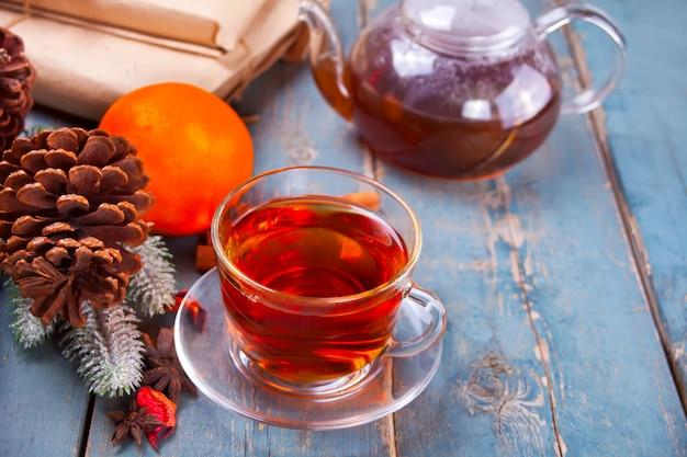 Tasse tee und teekanne auf einem hölzernen hintergrund.