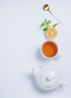 Tasse tee und teekanne mit zitrone und minze auf weißem hintergrund. draufsicht und kopierraum