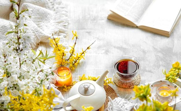 Tasse tee und teekanne zwischen frühlingsblumen und brennenden kerzen