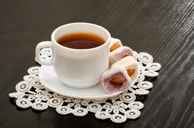 Tasse tee und türkische freude mit nüssen auf einer platte, nahaufnahme, schwarz