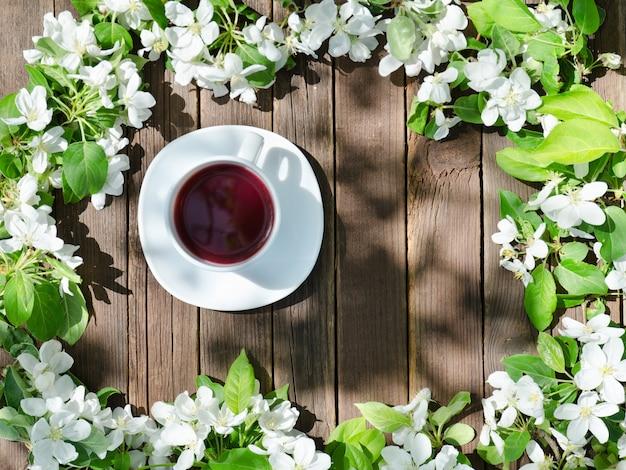 Tasse tee unter apfelblüte auf einem holztisch. ansicht von oben