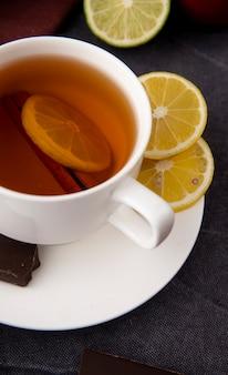 Tasse tee von der seitenansicht mit dunkler zitrone-zimt-schokolade und limette auf schwarzer oberfläche