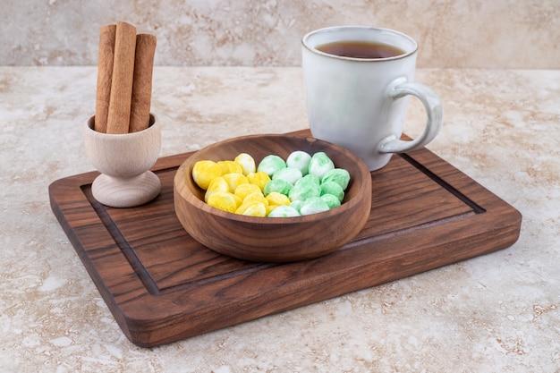 Tasse tee, zimt und bonbons auf holzbrett