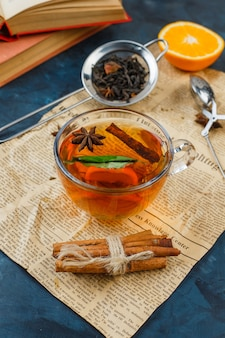 Tasse tee, zimt und teesiebe mit zeitung, orange und einem buch auf blauer marmoroberfläche