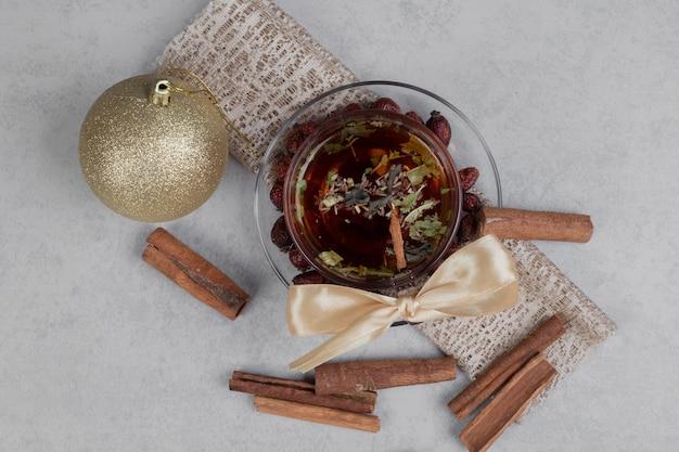Tasse tee, zimtstangen und festliche kugel auf weißem tisch. hochwertiges foto