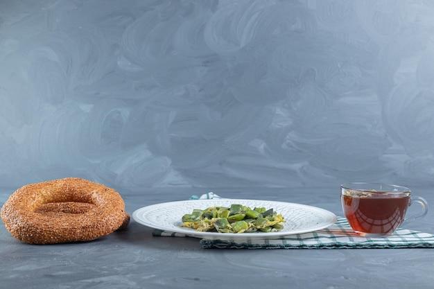 Tasse tee, zwei bagels und eine platte mit gekochten bohnenhülsenfrüchten gemischt mit rührei auf marmortisch.