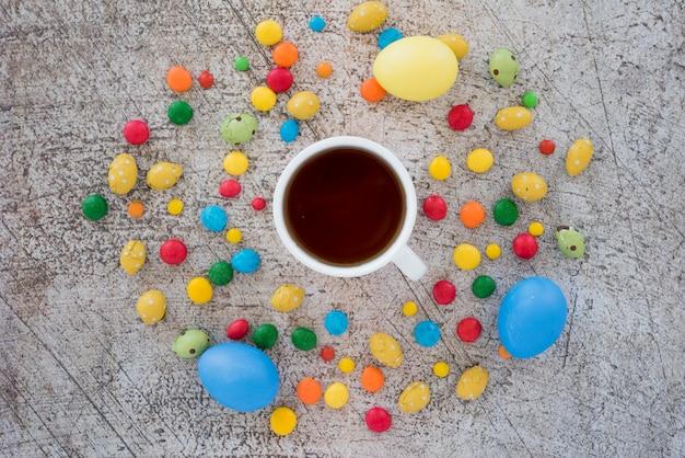 Tasse tee zwischen mischung von süßigkeiten und eiern