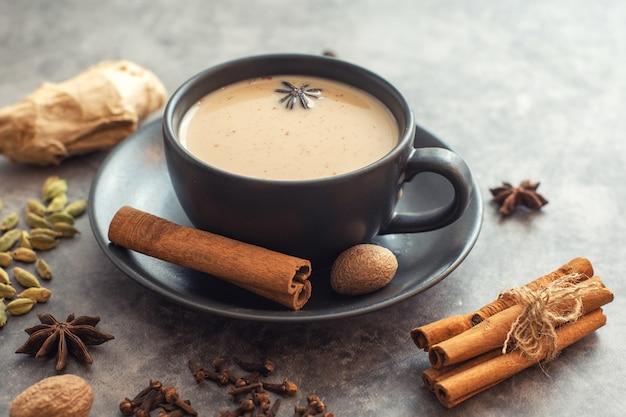Tasse traditionellen indischen masala chai tee mit zutaten. zimt, kardamom, anis, muskatnuss.