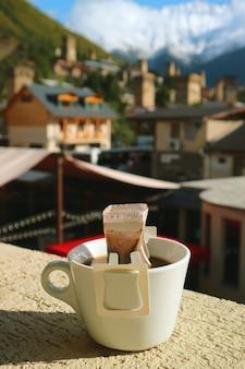 Tasse tragbaren filterkaffees, der am sitz im freien mit mestia town, kaukasus, georgia zubereitet wird