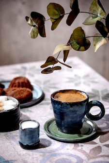 Tasse türkischer schwarzer kaffee mit milch, zuckerwürfeln und keksen auf kunstvollem keramiktisch mit eukalyptuszweigen