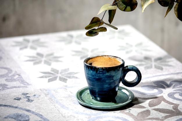 Tasse türkischschwarzer schaumiger kaffee auf kunstvollem keramiktisch mit eukalyptuszweigen