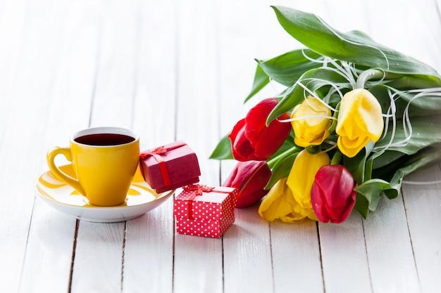 Tasse und geschenkbox mit tulpenstrauß