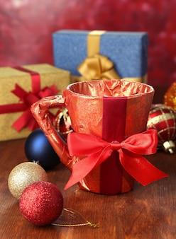 Tasse verpackt in geschenkpapier mit geschenken auf holztisch auf hellem hintergrund
