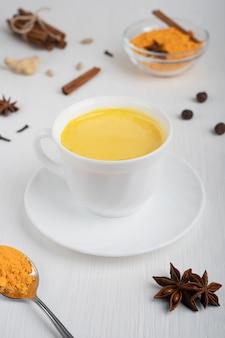 Tasse voll goldener milch serviert auf teller mit löffel kurkuma und anis auf weißem holztisch