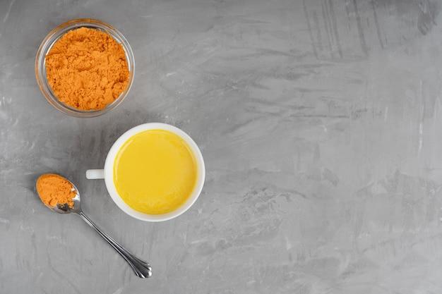 Tasse voll goldener milch serviert mit löffel und schüssel kurkuma auf grauem betonhintergrund