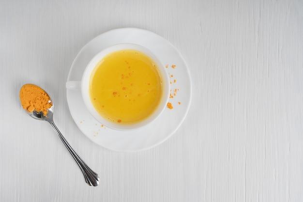 Tasse volle kurkuma-milch serviert auf teller mit löffel curcuma auf weißem holztisch