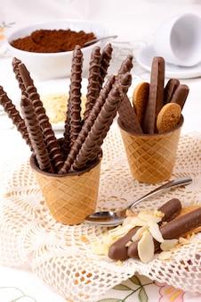 Tasse waffel schokolade kakaopulver und mandel in scheiben geschnitten und schokostick