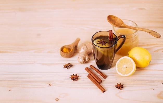 Tasse warmes wasser mit zitrone, honig, ingwer, zimt und anis.