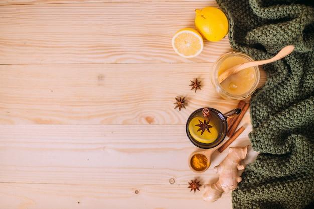 Tasse warmes wasser mit zitrone, honig, ingwerwurzel, zimt und anis.