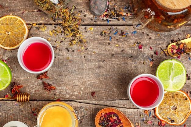 Tassen des gesunden kräutertees mit zimt-, getrockneten rosen- und kamillenblumen in löffeln über hölzernem hintergrund, draufsicht