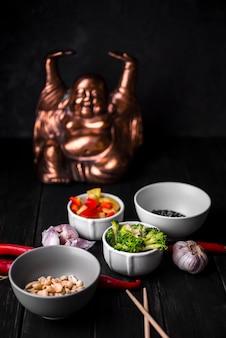 Tassen gemüse mit statue und erdnüssen
