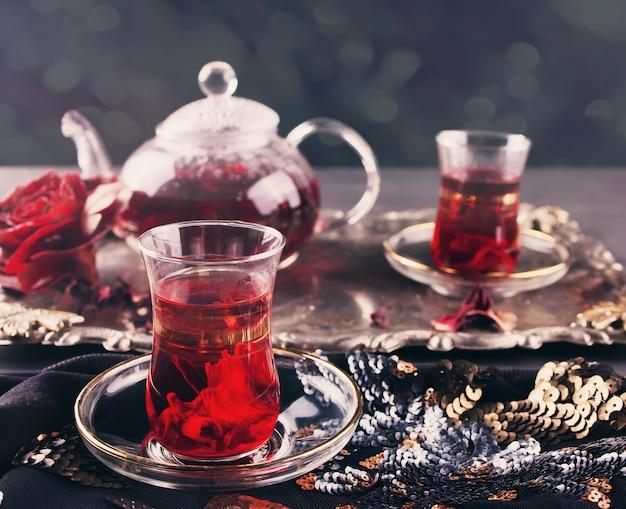 Tassen heißer roter karkade tee mit teekanne auf dem tablett