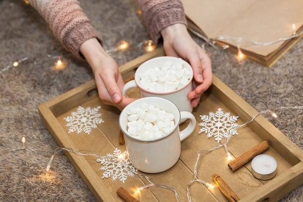 Tassen kaffee mit marshmallow auf weihnachtstablett, weicher fokus