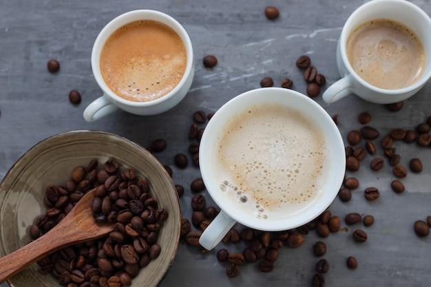 Tassen kaffee mit milch und körnern auf keramikhintergrund